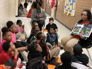 Teacher reading to students in the hallway.