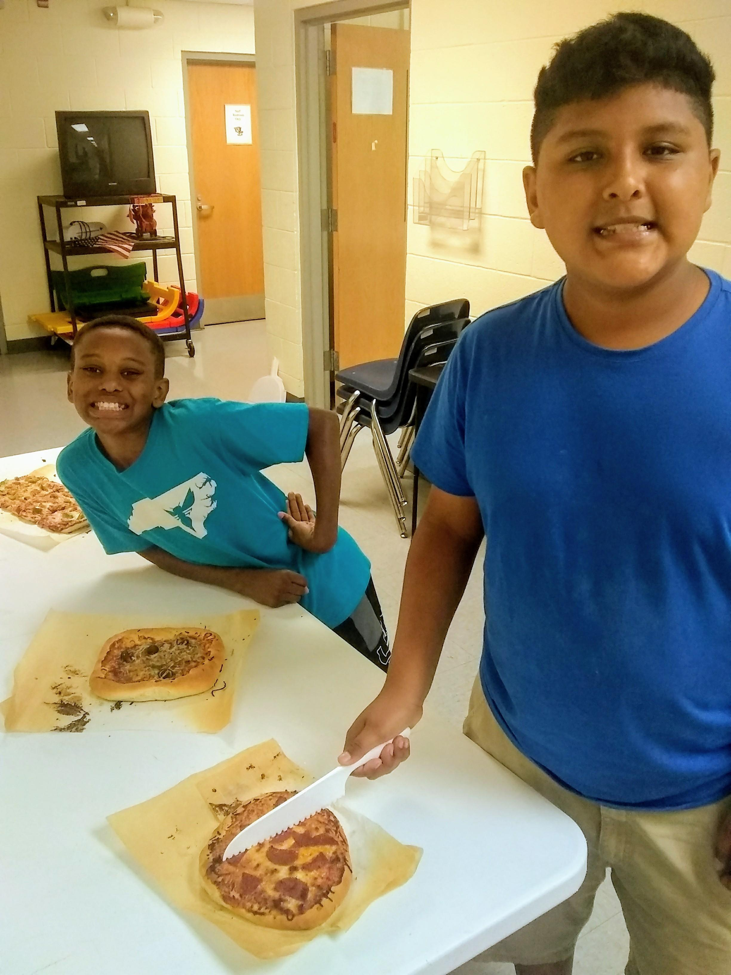 kids with their cooked pizzas