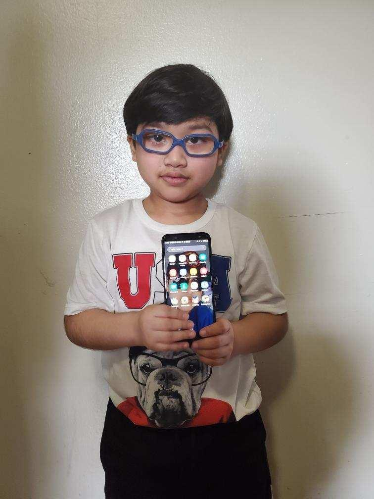 boy with glasses holding up a cell phone