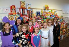 Several students dressed in Halloween Costumes standing in front of cereal boxes