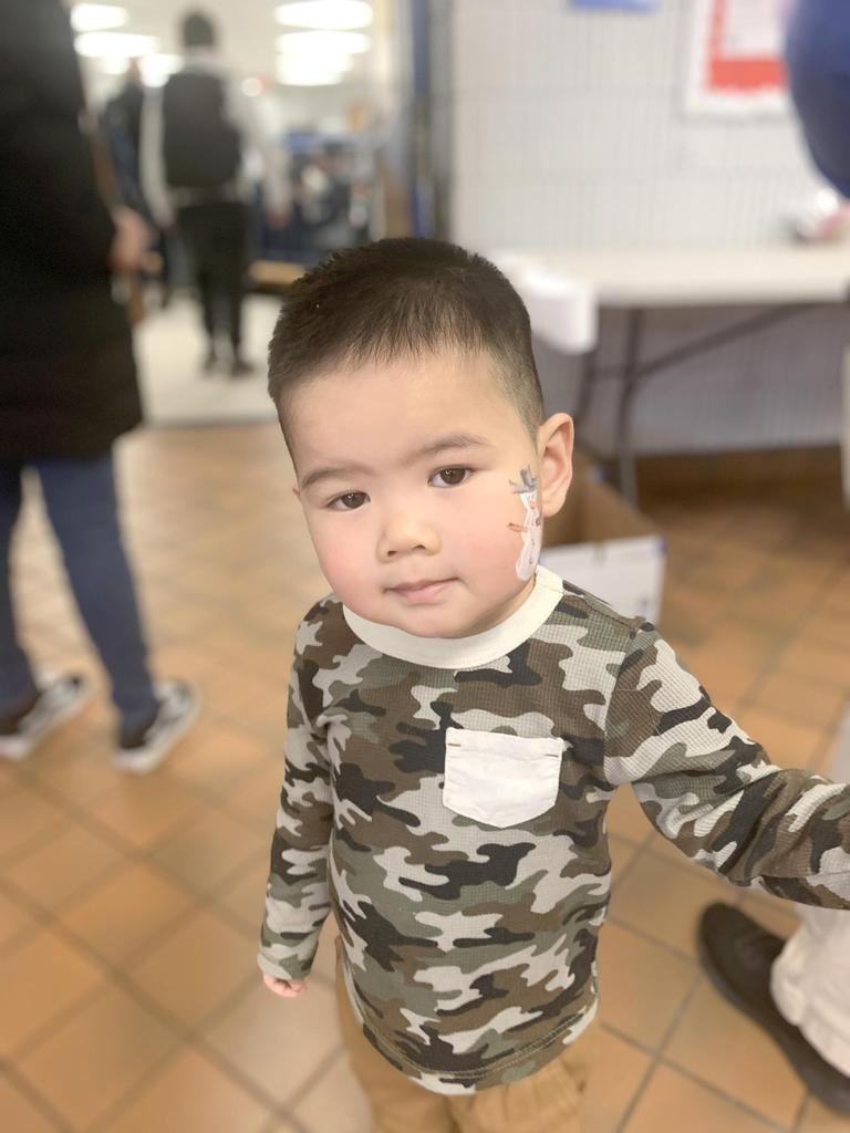 A young student in a camouflage shirt, with a temporary tattoo of a snowman on his cheek
