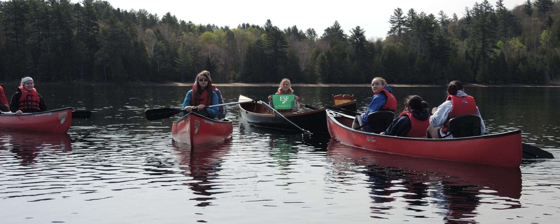Four canoes full of the Environmental Club students paddle around a lake