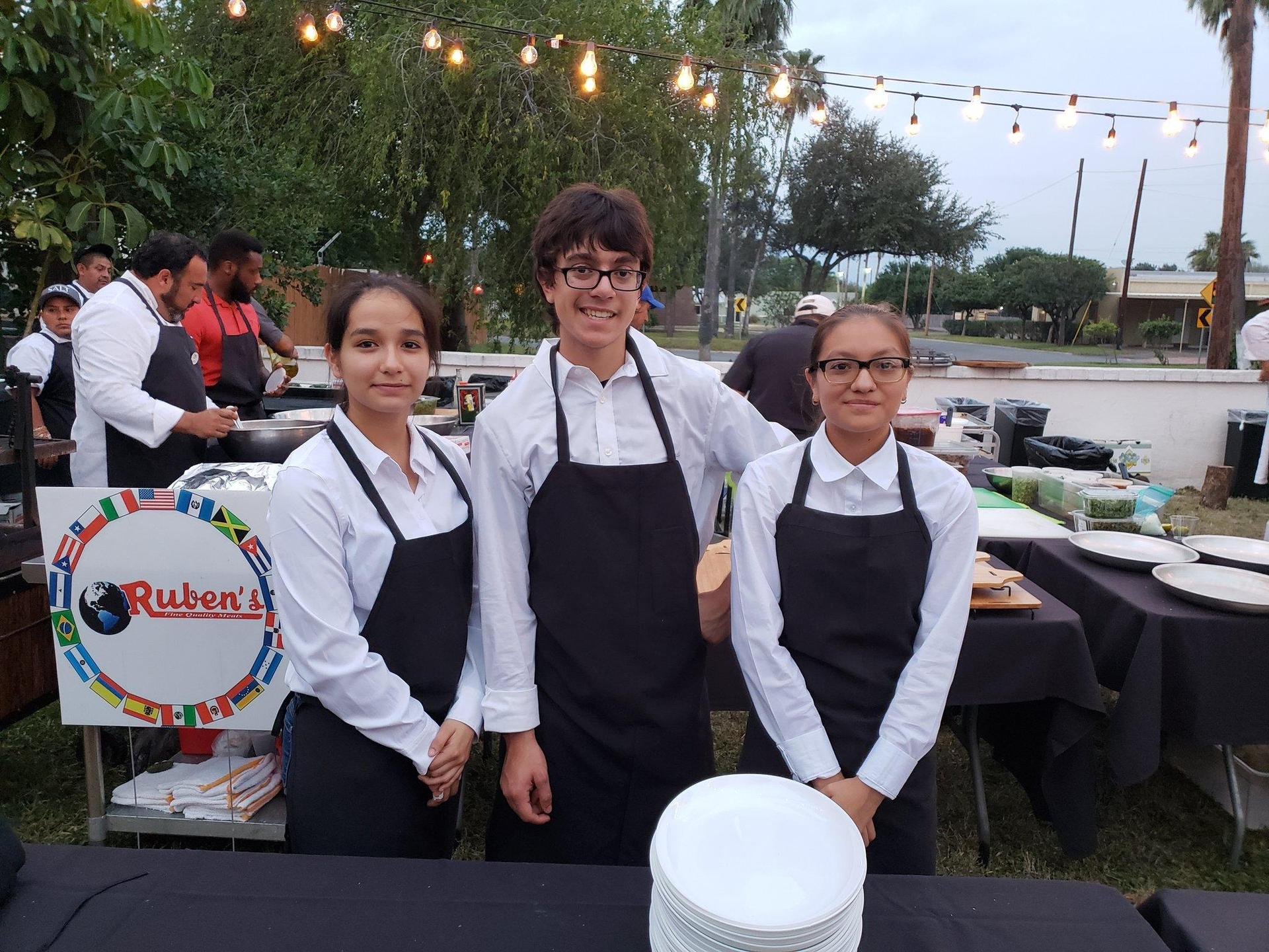 three individuals in cooking aprons posing
