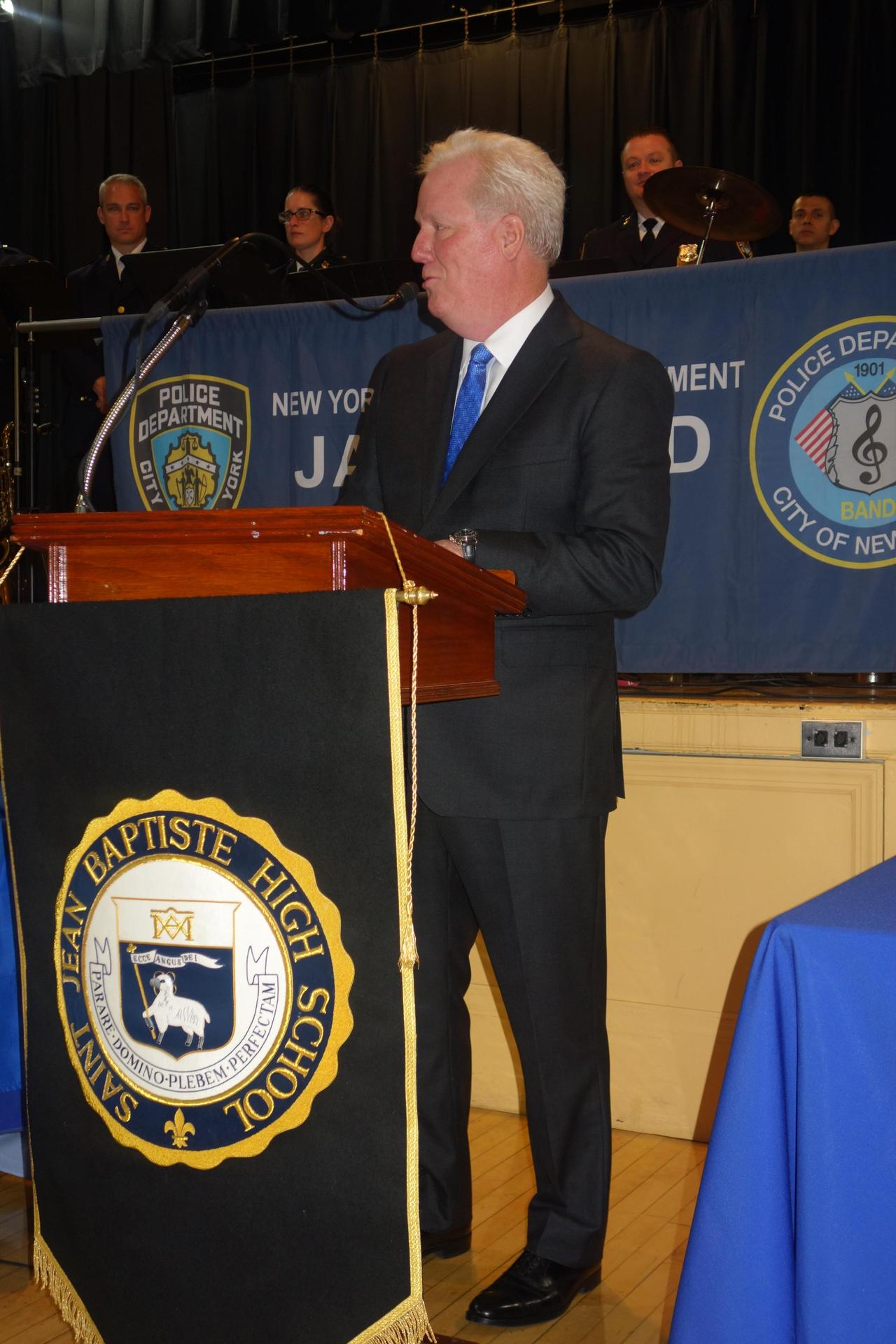 Man in suit with white hair speaks from wooden podium with navy blue banner with crest of lamb