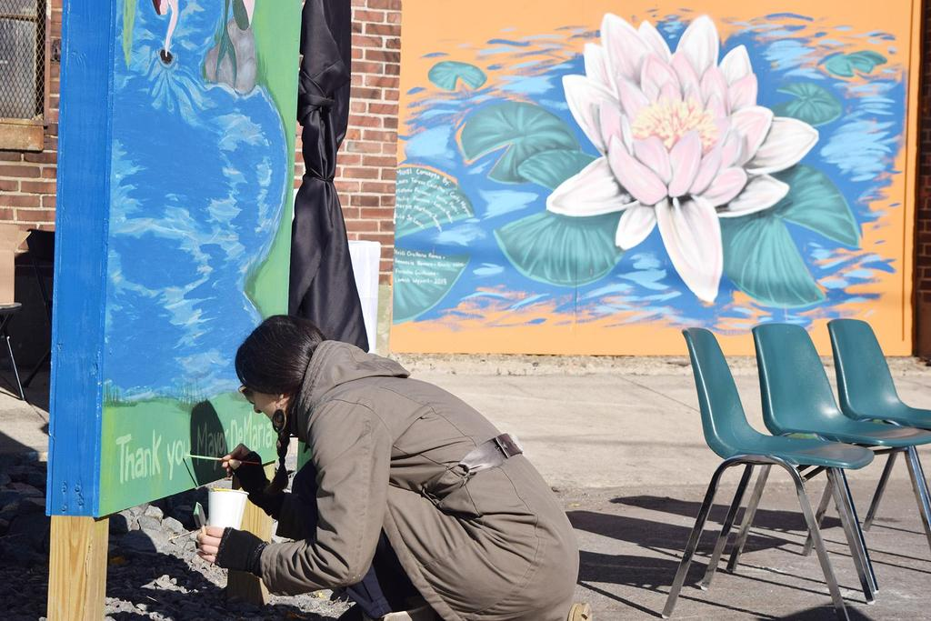 An artist paints the words 'Thank you Mayor DeMaria' at the bottom of a piece of artwork