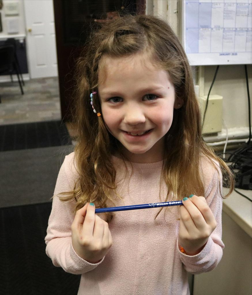"Photo of Wilson 1st grader holding a special Wilson pencil, awarded to her as an ""Ambassador of Kindness."""