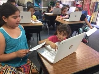 2 students typing on Chromebooks