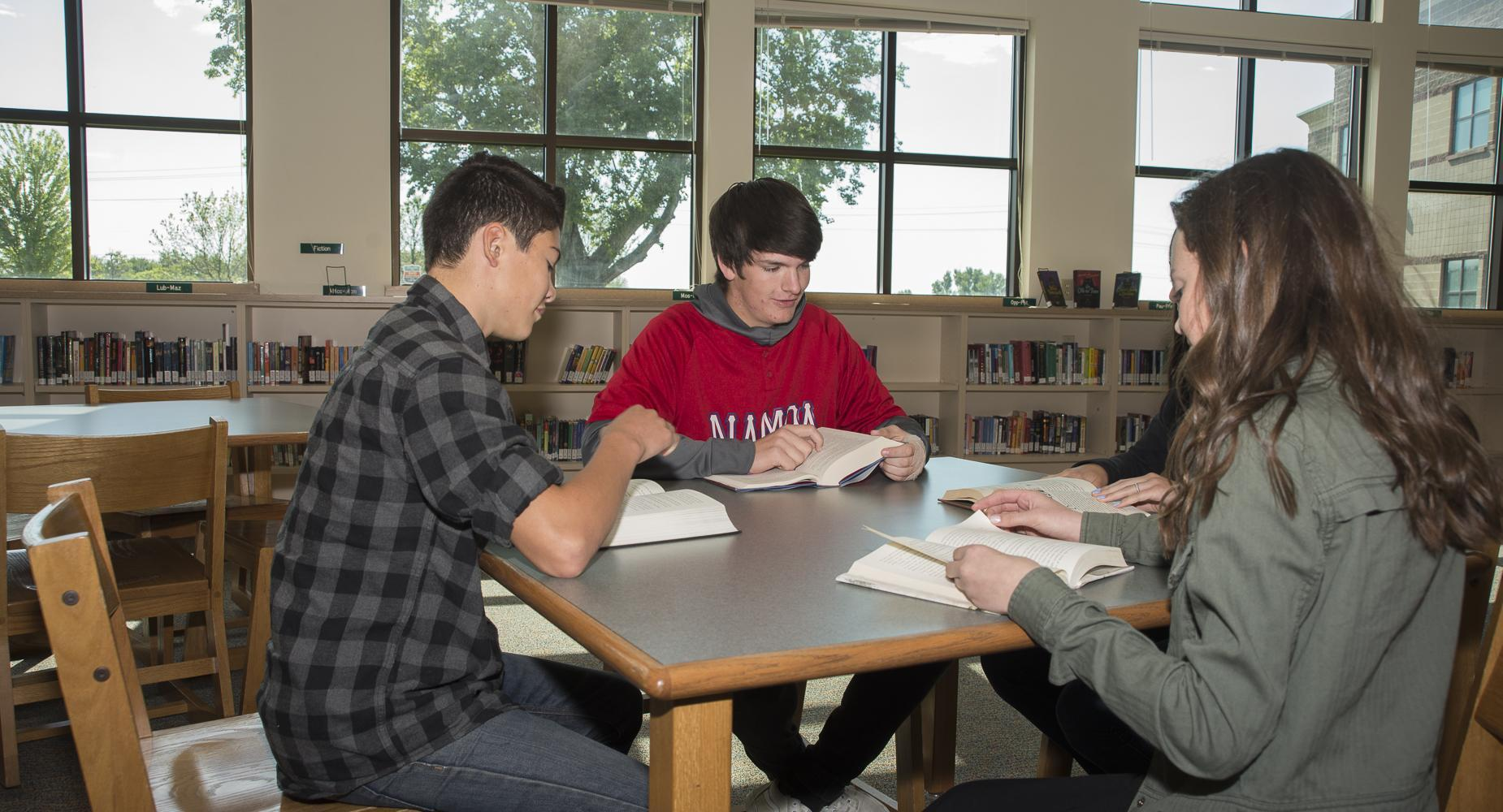 Three students study at a table in the library