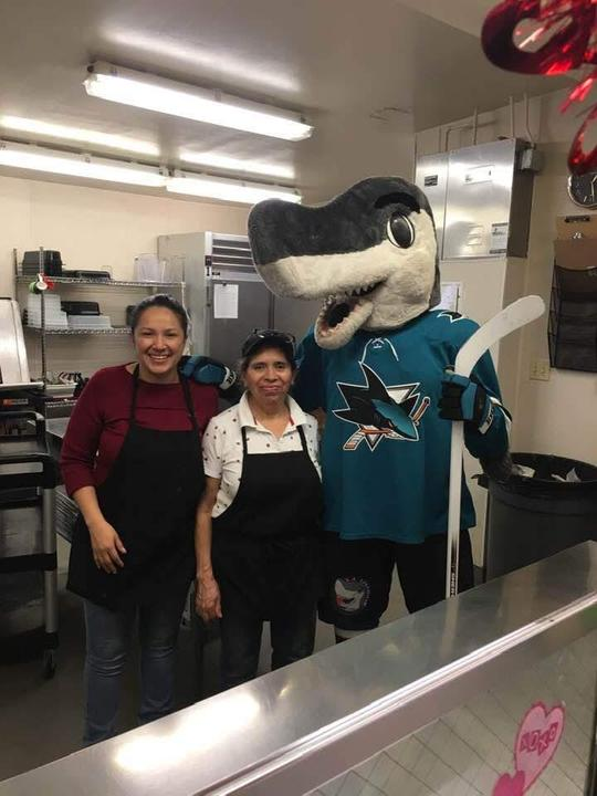 cafeteria workers smile while posing with sharkey the sharks mascot