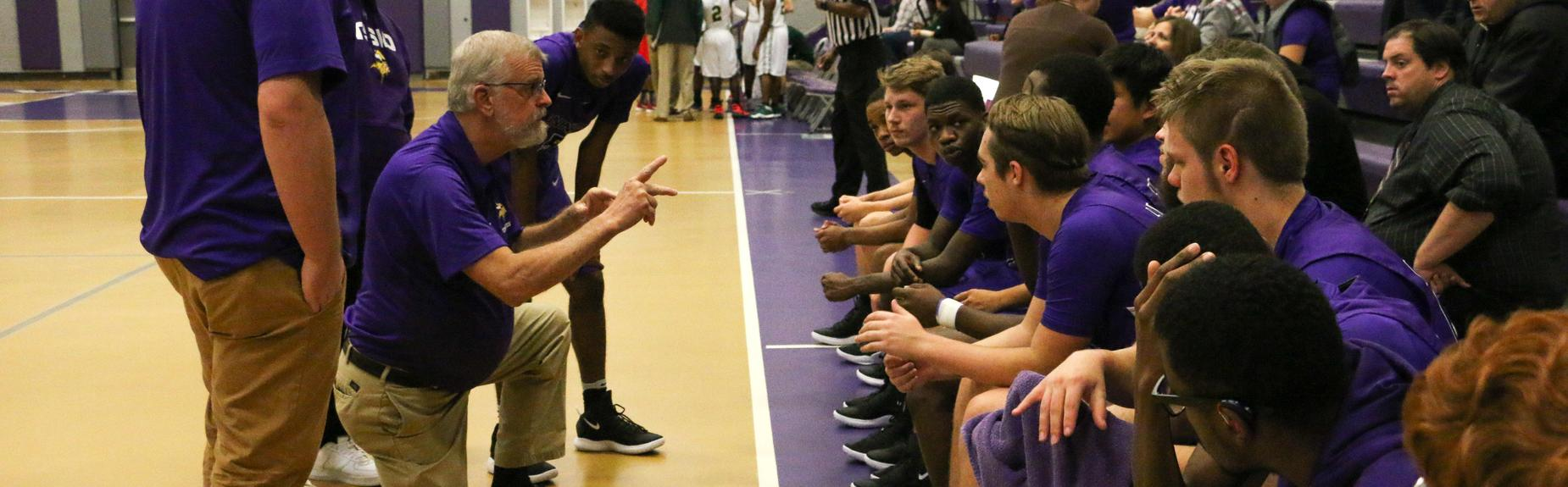 Boys's varsity basketball team during timeout to meeting w their coach in sign languages.