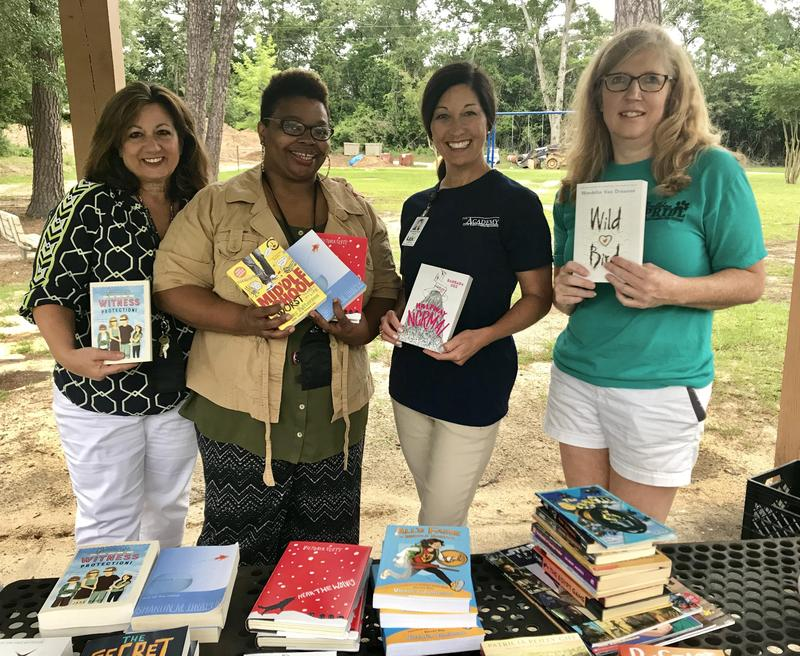 From left, Busbee teacer Donna Wilmot, counselor Auketa Govan, Principal Stephanie Smith Hucks and teacher Lisa Fisher set out books for Wednesday's inaugural summer reading event.
