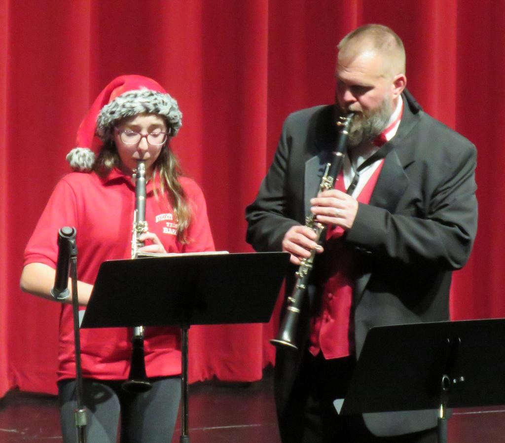 A student and a teacher both play the clarinet