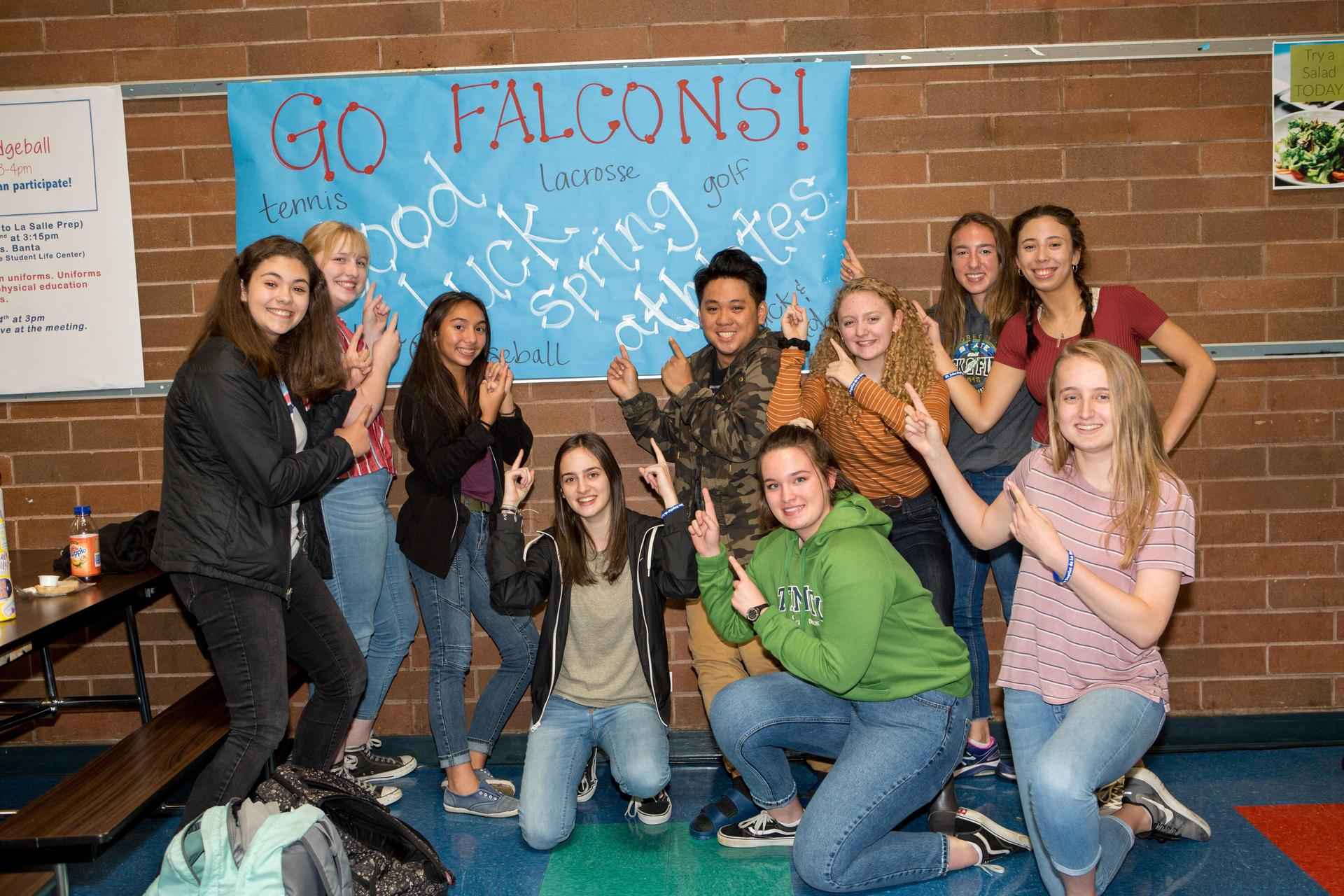 group of students pointing at Go Falcons sign