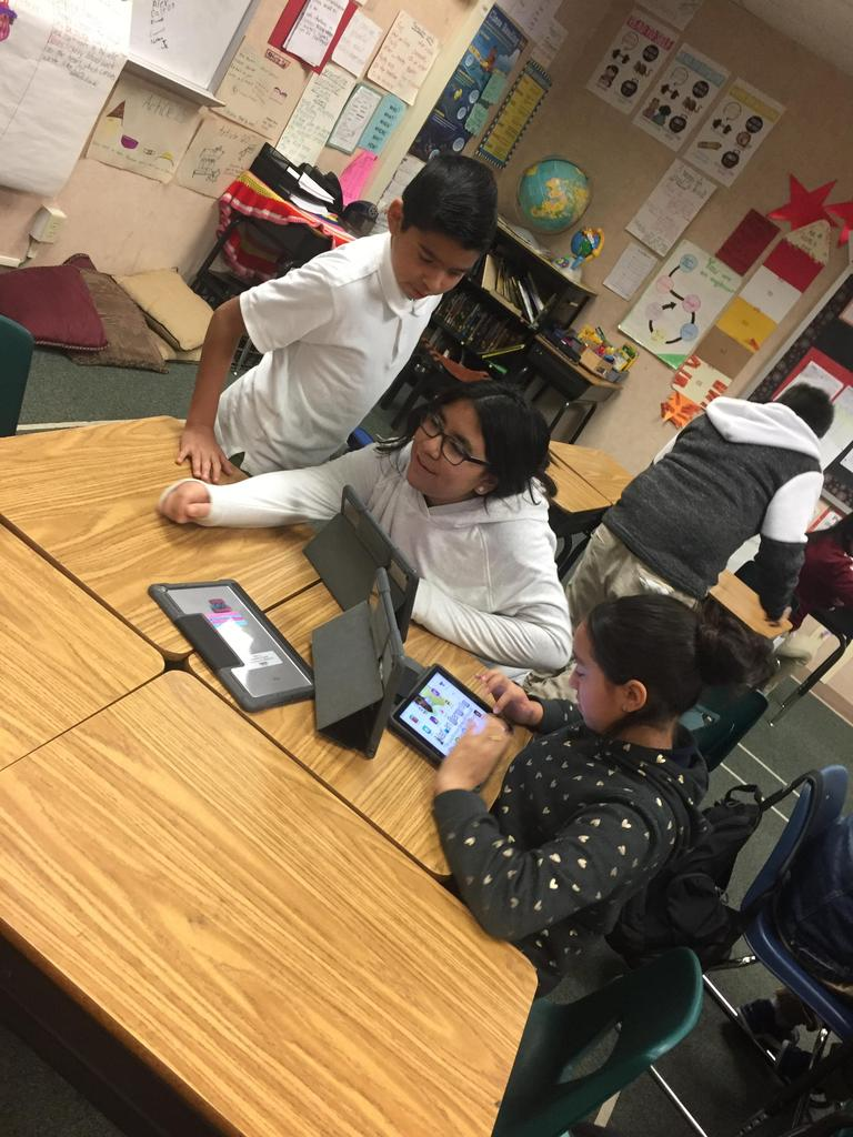 students smile as they do coding on iPads
