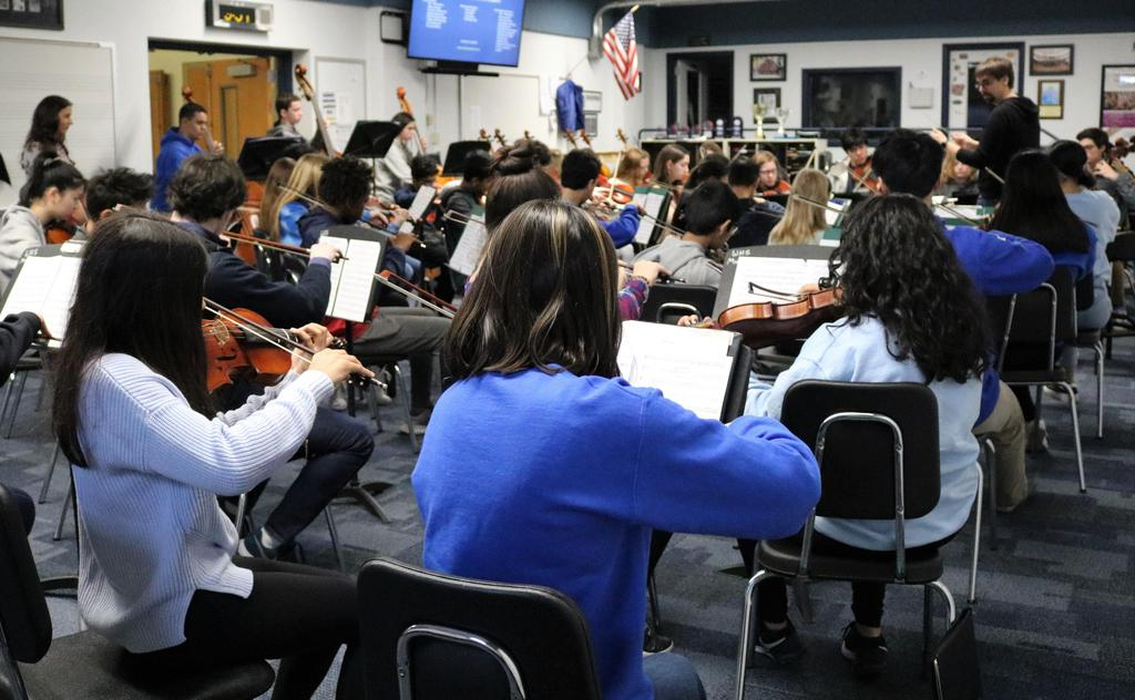 Photo of WHS orchestra director working with high school and intermediate school student musicians during District Music Day