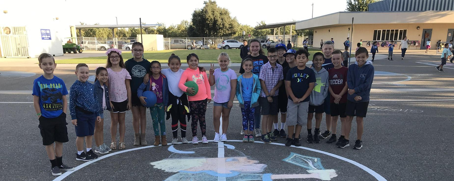 Kids pose with Viking art on basketball court