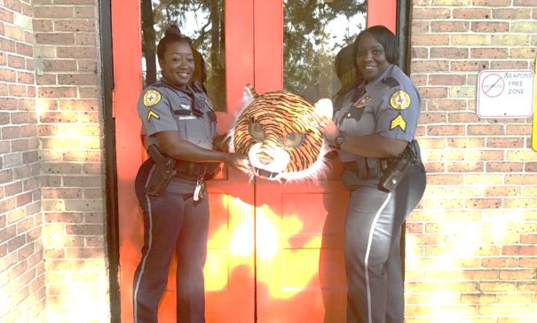 Police officers holding tiger head