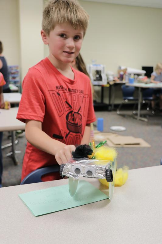 a student shows off his robot on wheels