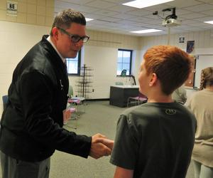 TKHS Principal Tony Petersen greets a student before the mock interview starts.