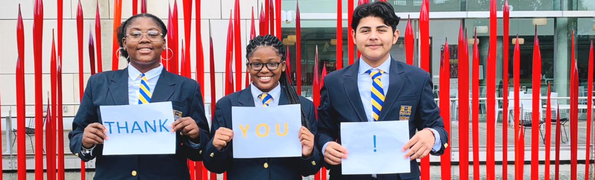 "Cristo Rey Richmond students pose with ""thank you"" signs near campus."