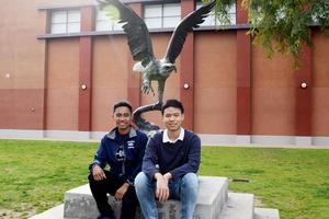 Two GHS students pose in front of the eagles statue.