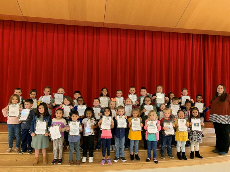 group picture of PreK, kindergarten, and first grade students that received character kid awards for the 2nd six weeks. Pictured on the stage with the counselor.