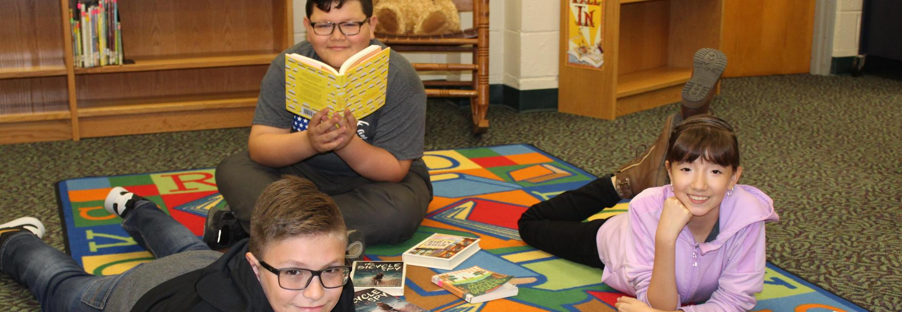 kids on carpet with books