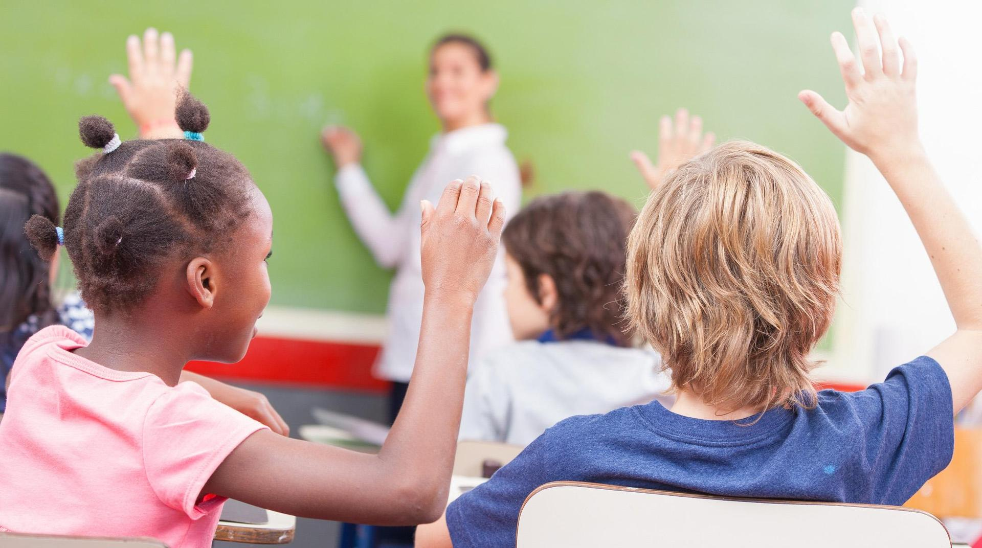 Students with their hands raised, with a teacher at the head of the class