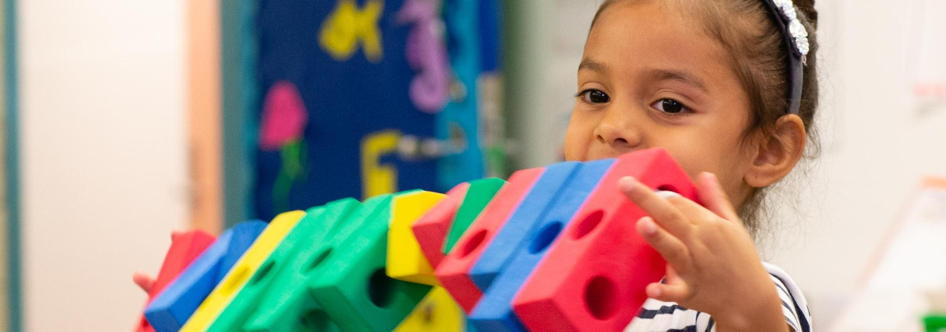 A pre-k student holding a row of blocks.