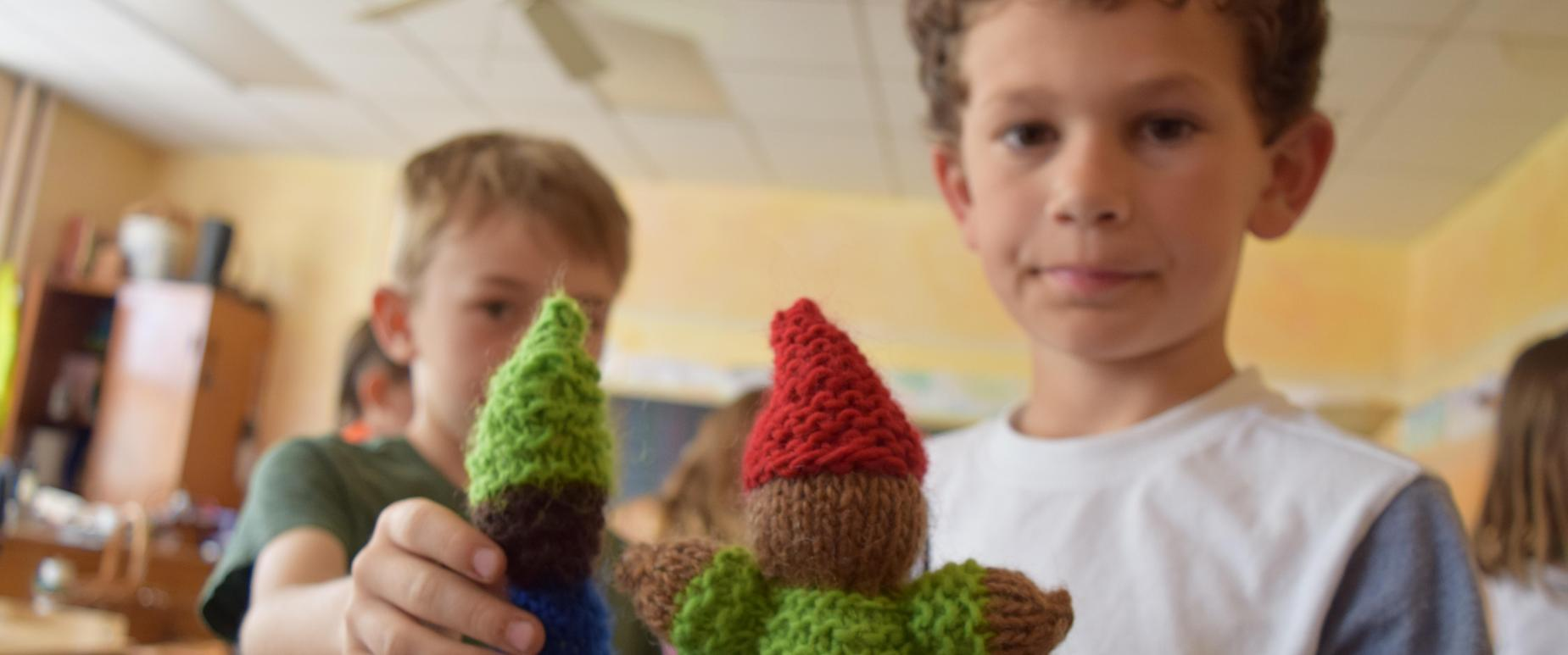 second grade students show their hand knit gnomes
