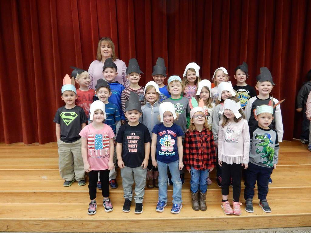 Mrs. Boswell's Kindergarten with Mrs. Teaster,  dressed as Pilgrims and Native Americans, standing together on the stage.