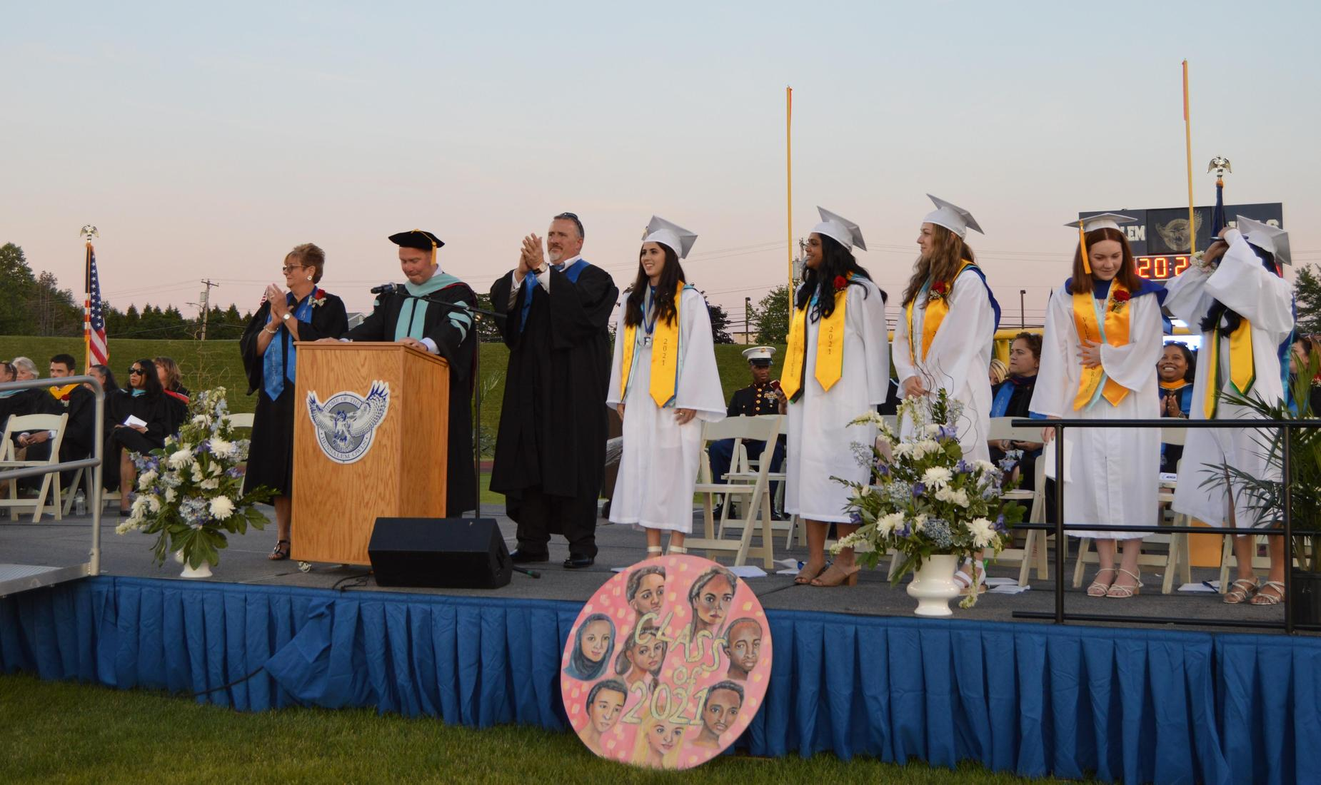 BHS Class of 2021 Commencement - 5 female seniors in white caps and gowns standing on the dais