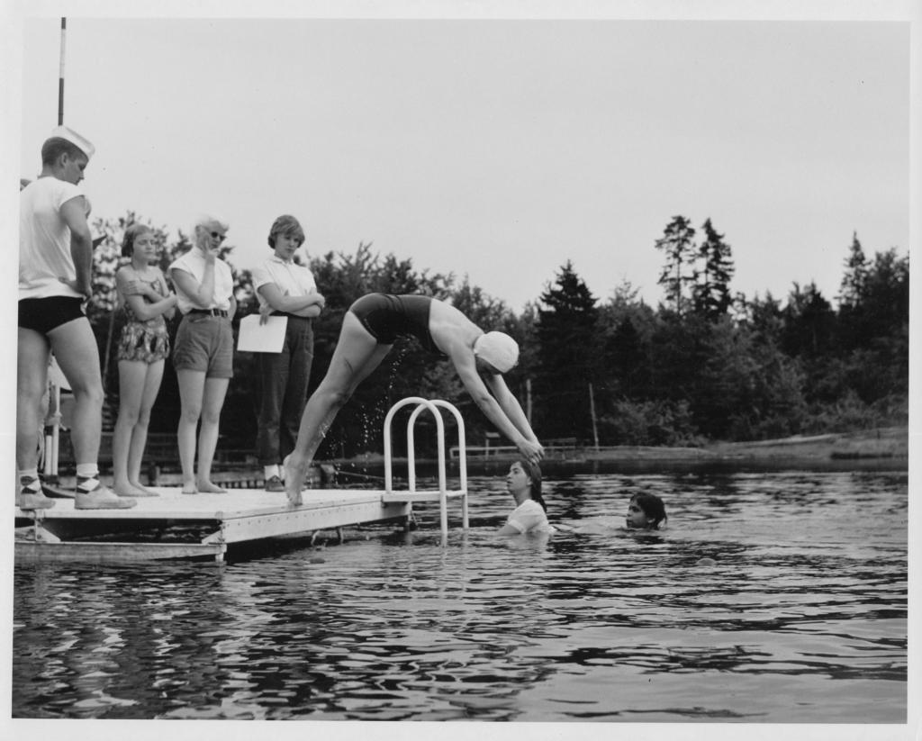 Circa 1950, girls at the lake diving into it.