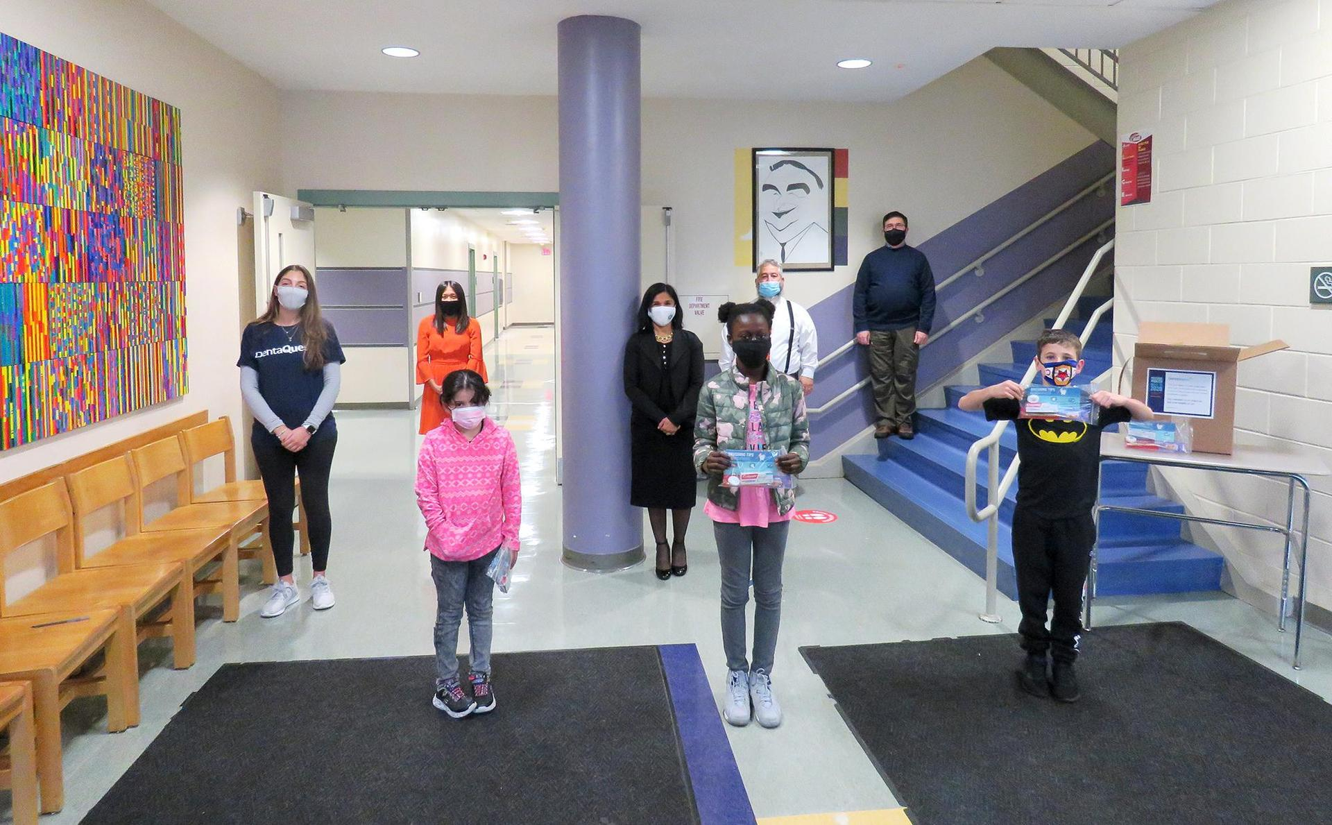 Students and adults, standing, socially distanced, in the Keverian School lobby