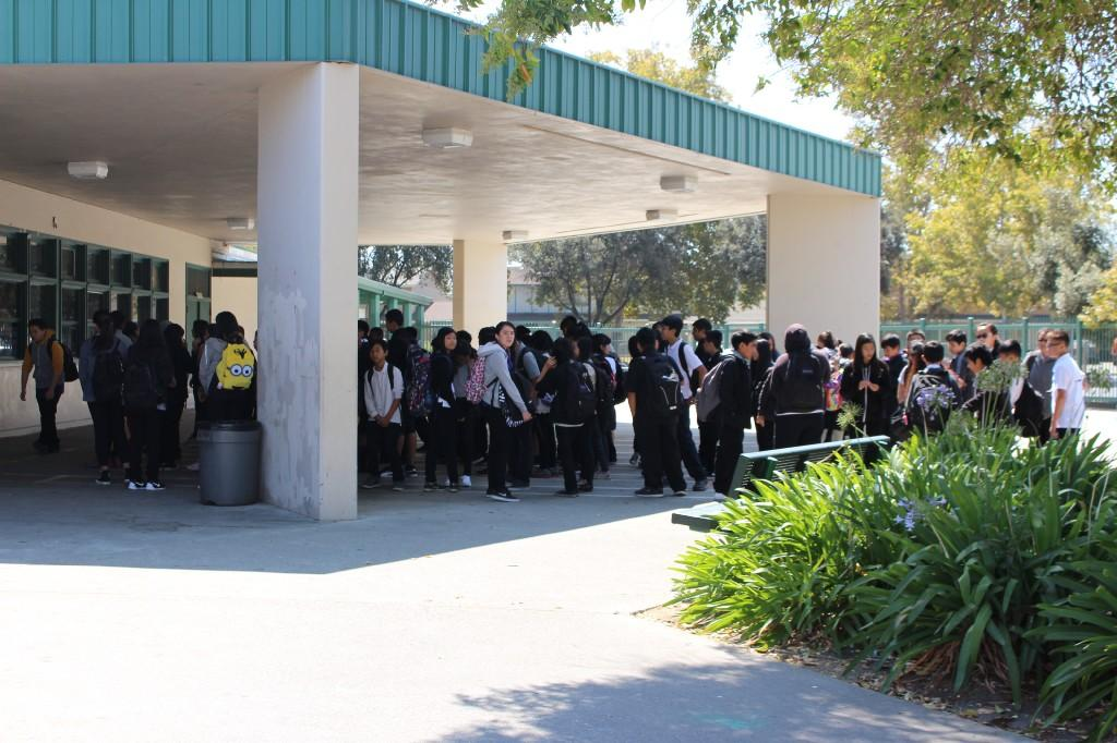 several students standing in line in front of a school cafeteria