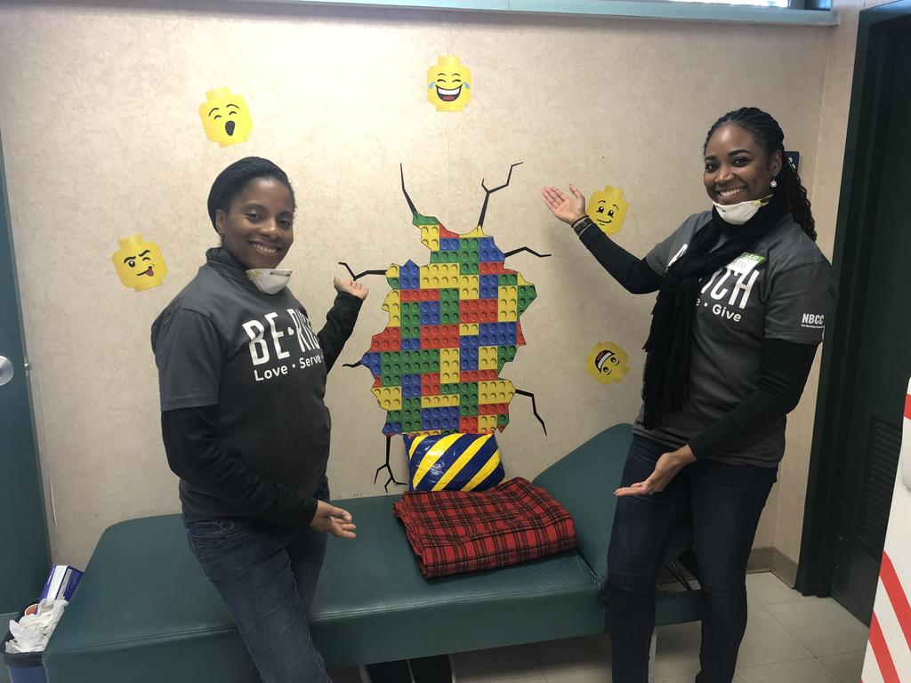 two NBCC members show off wall decor in nurse's office