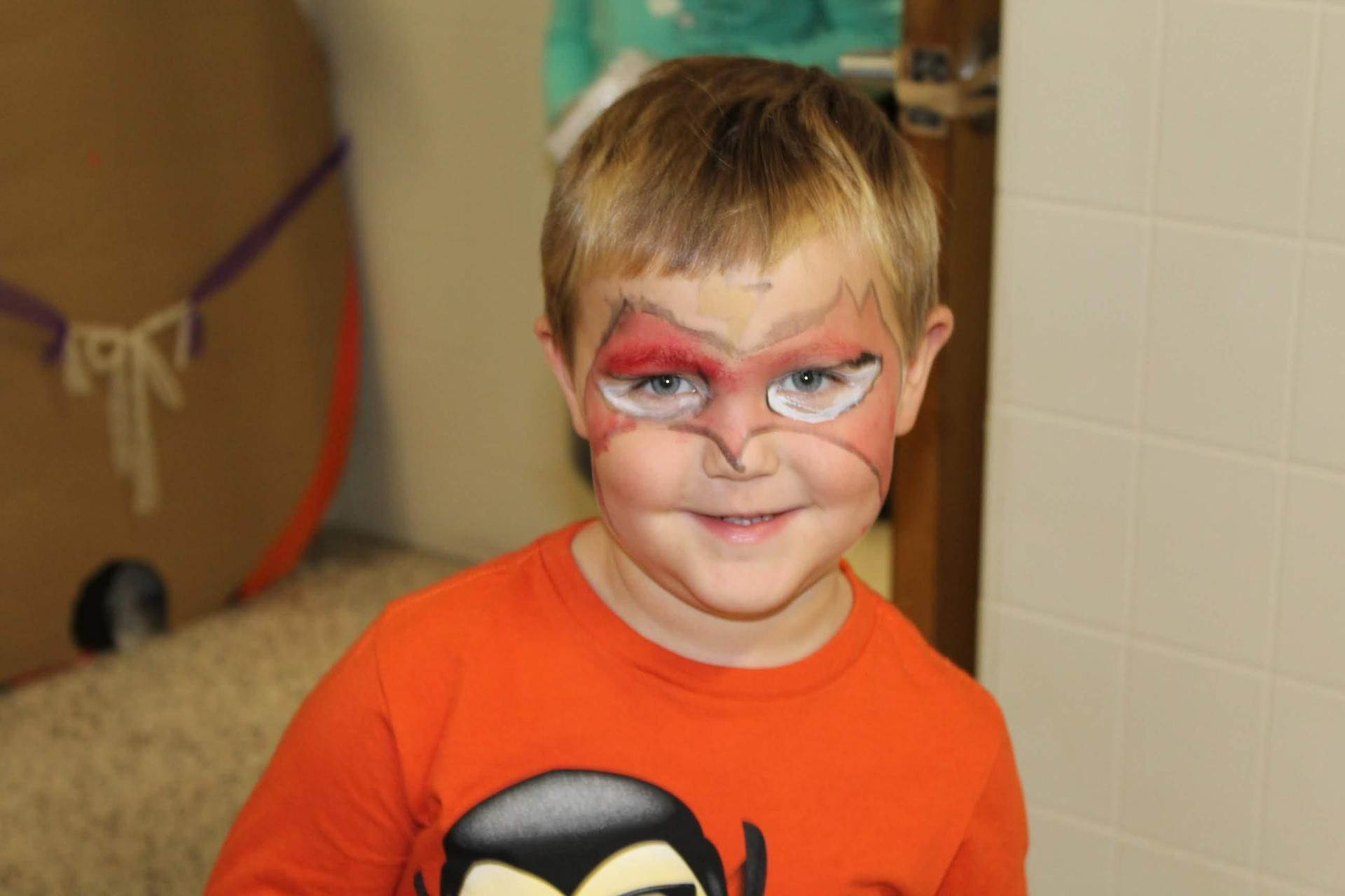 Student with superhero mask painted on his face during fall festival.