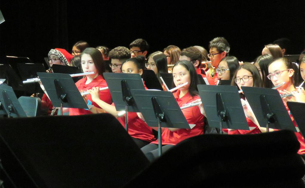 Multiple members of a middle school band play a holiday favorite