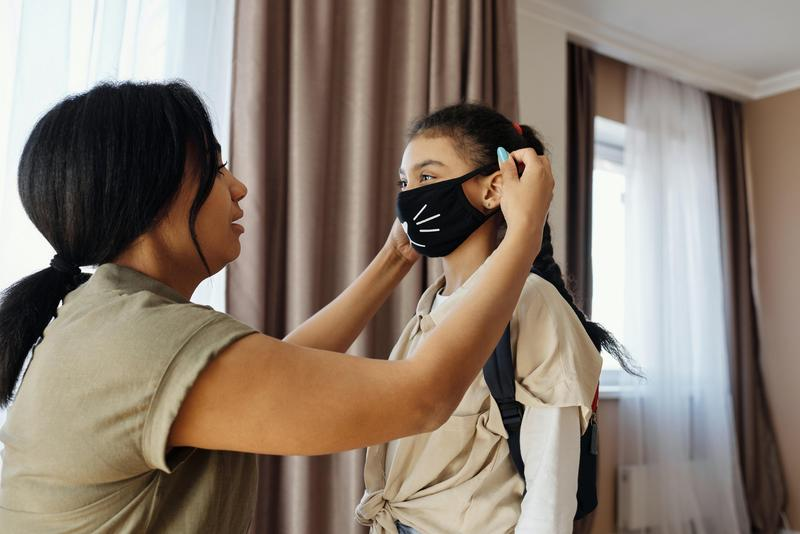 Parent putting mask on a child