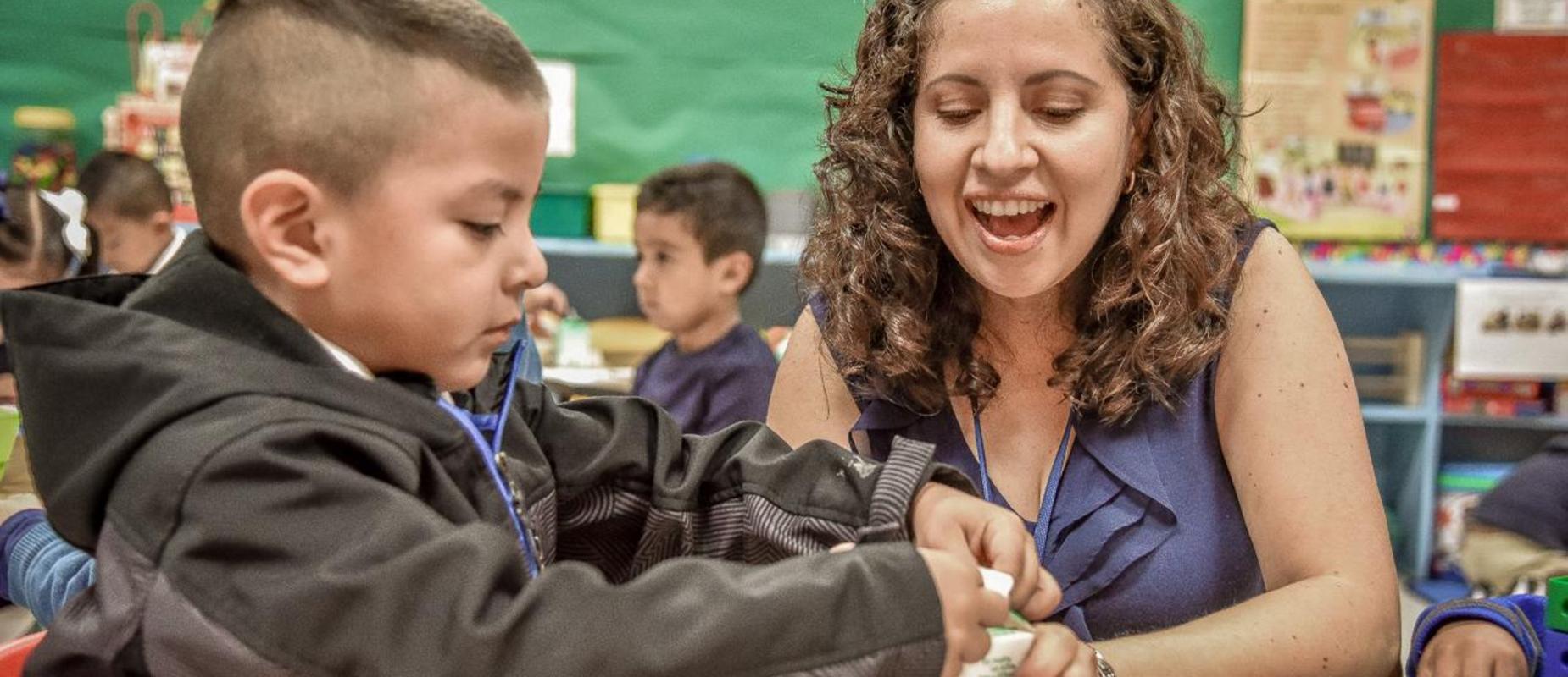 A teacher helping a student open his milk