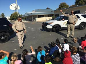 two CHP officers presenting to young students