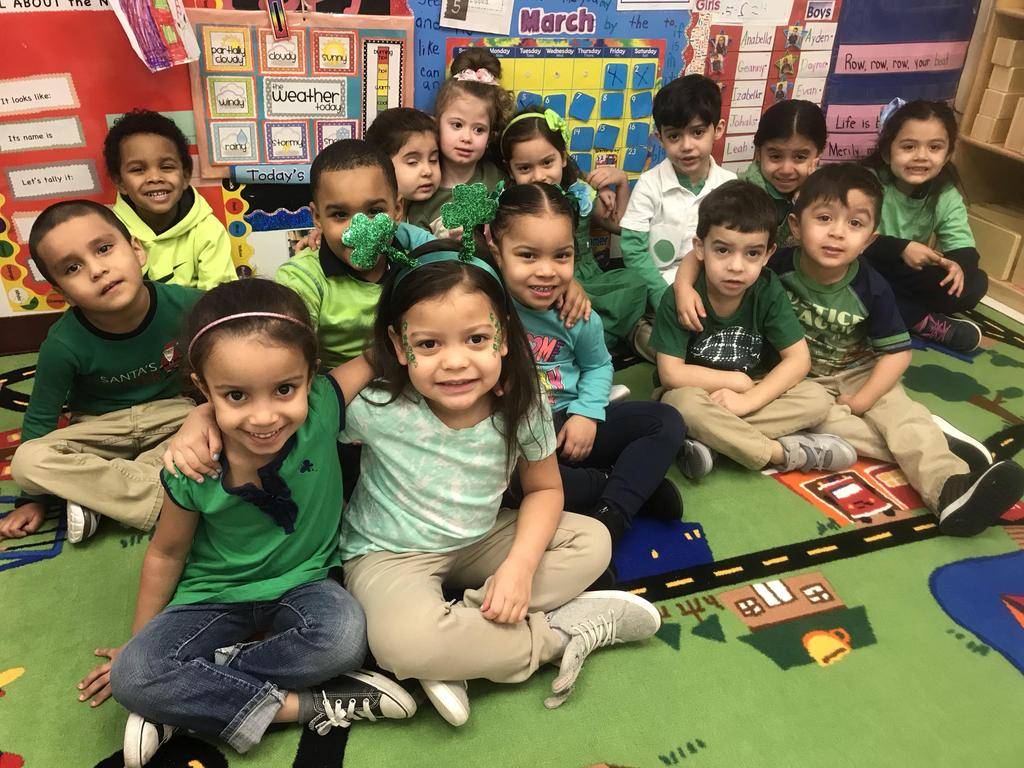 Pre-K class wearing green and sitting on the class rug