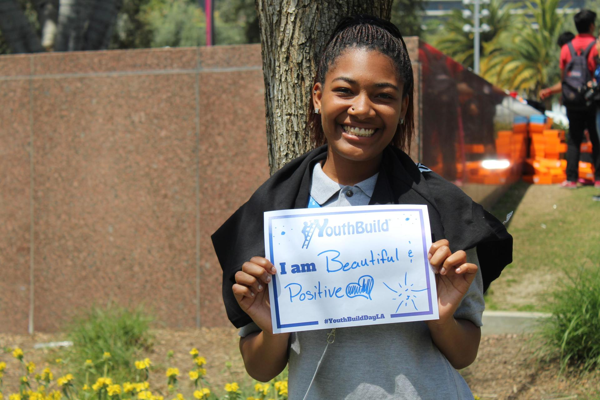 A South LA student holding a sign that says 'I am beautiful and positive'