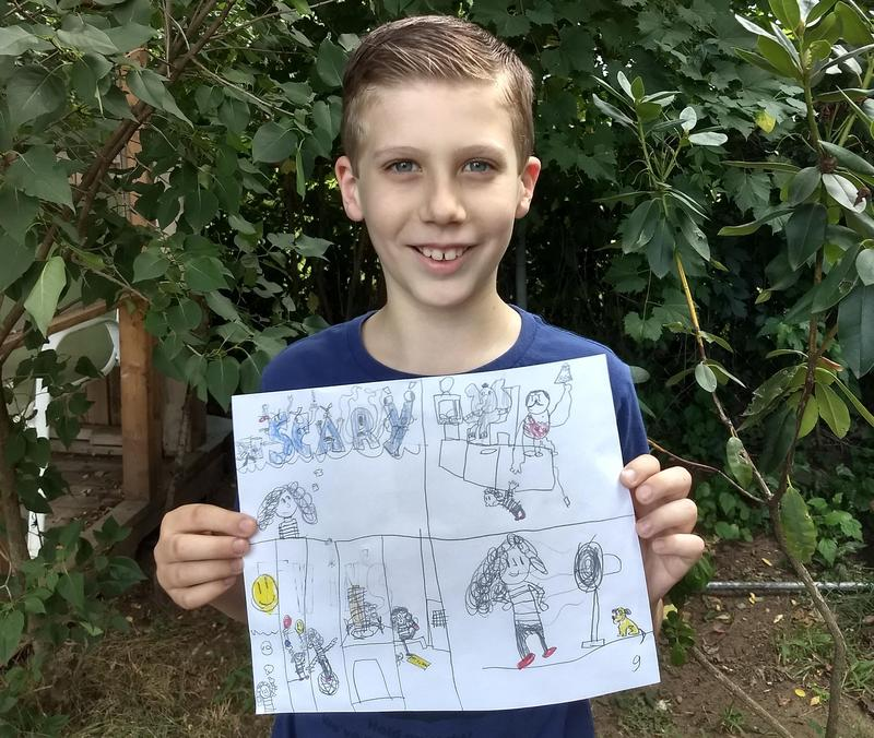 Levi with a picture of his drawings.