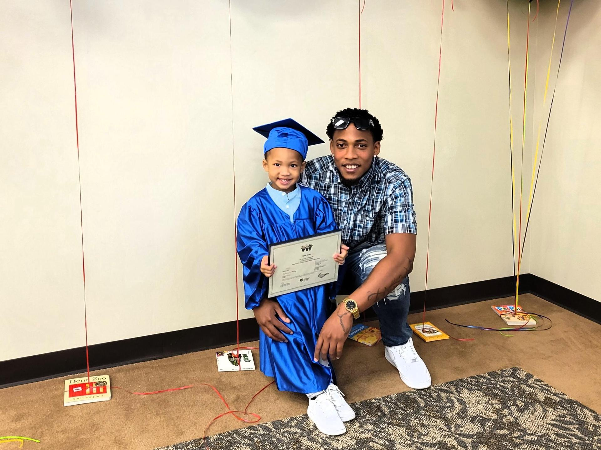 Father and son stand with Help Me Grow/Every Child Succeeds graduation certificate