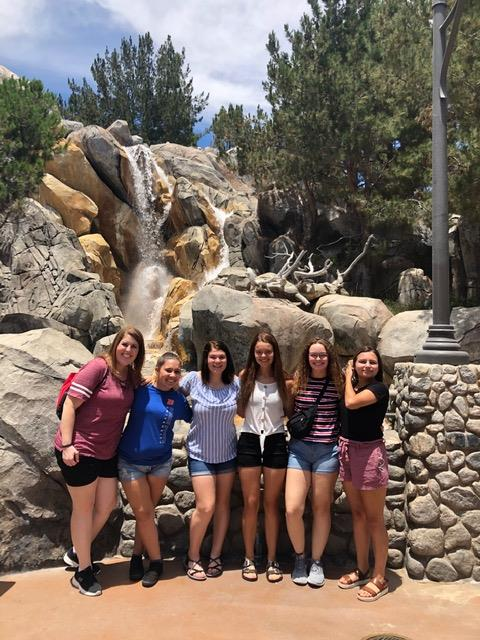 Kylee Miller, Gracie Studer, Alexus Hill, Jasmine Ondesko and Anastasia Jones pose at Disneyland with advisor Allison Hinshaw.