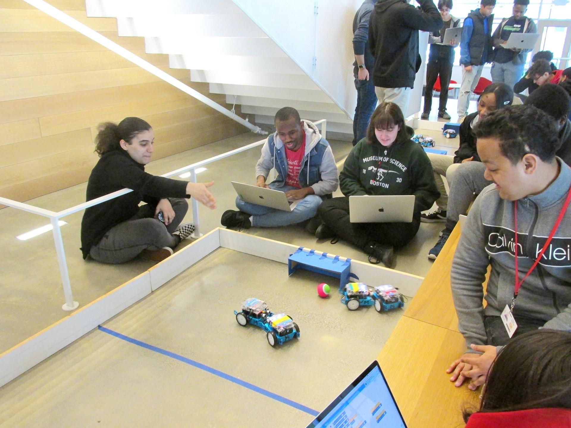 Students seated on the ground, looking at robotics devices