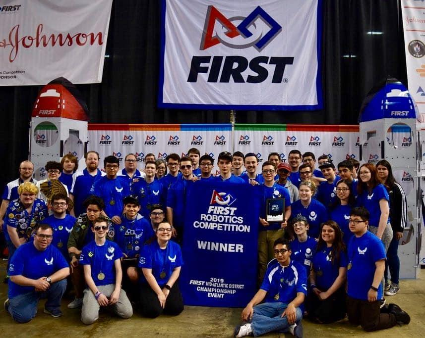 High School Robotics Team dressed in royal blue shirts holding banner recognizing them as champions