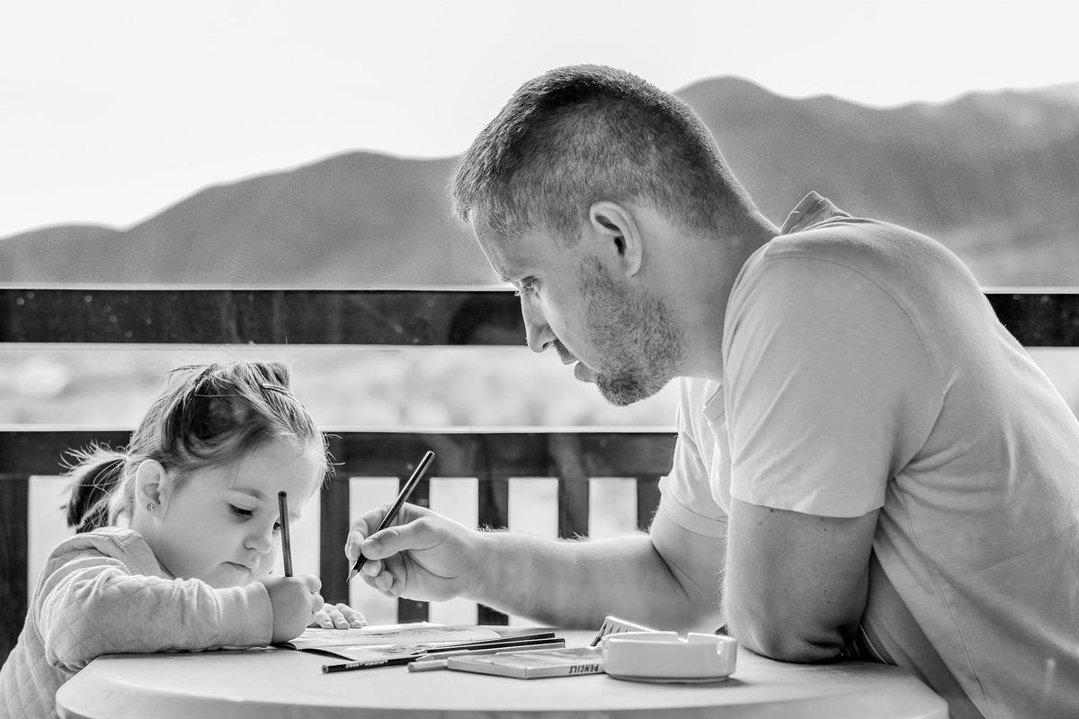 photo of father and daughter doing homework