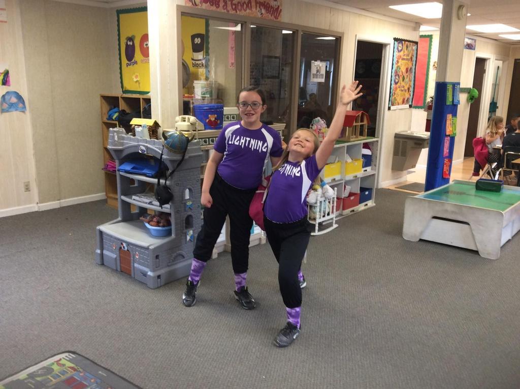 girls wearing softball uniforms